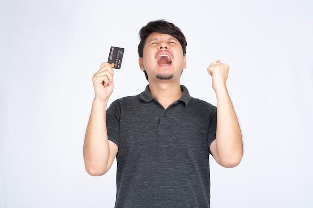 Uomo asiatico che tiene una carta di credito con un'espressione triste e delusa.