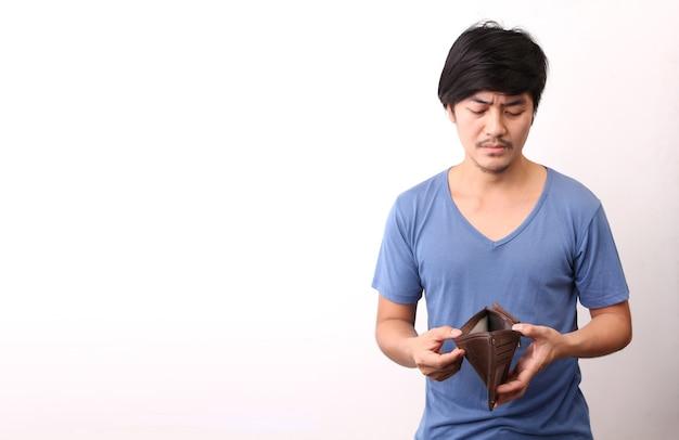 Uomo asiatico che tiene un portafoglio vuoto su priorità bassa bianca.