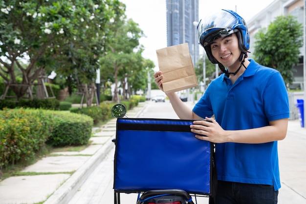 Uomo asiatico che tiene in mano un sacchetto di carta per alimenti e in piedi sul lato della scatola di consegna