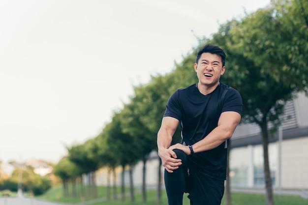 Uomo asiatico che tiene dolore al ginocchio dopo la corsa e il fitness, forte dolore alle gambe
