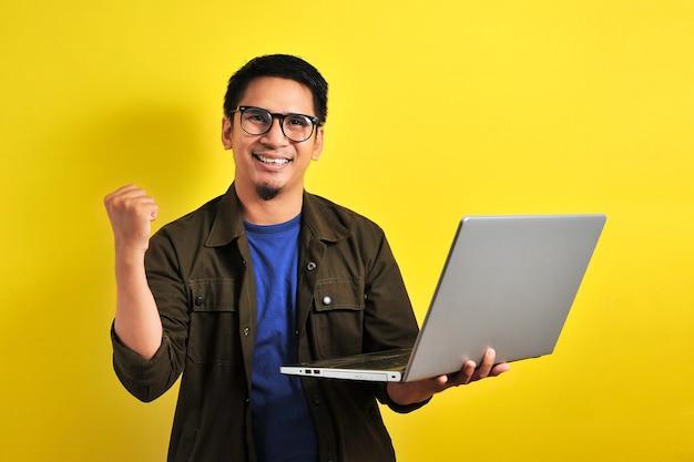 Uomo asiatico che tiene il computer portatile con gesto vincente. regalo o lotteria vincente dell'uomo d'affari asiatico, su sfondo giallo