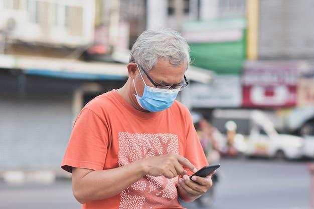 Uomo asiatico che tiene smart phone mobile utilizzare la maschera per proteggere il virus corona pm2.5 camminando sulla strada nuova normale distanza sociale