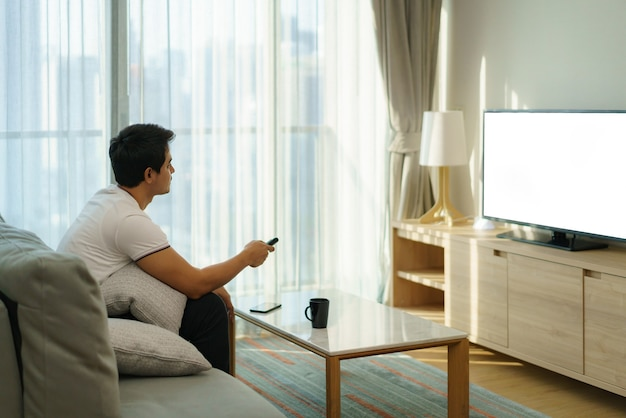 Un uomo asiatico tiene in mano un telecomando televisivo e sta premendo il canale mentre guarda la tv sul divano nel soggiorno di casa.