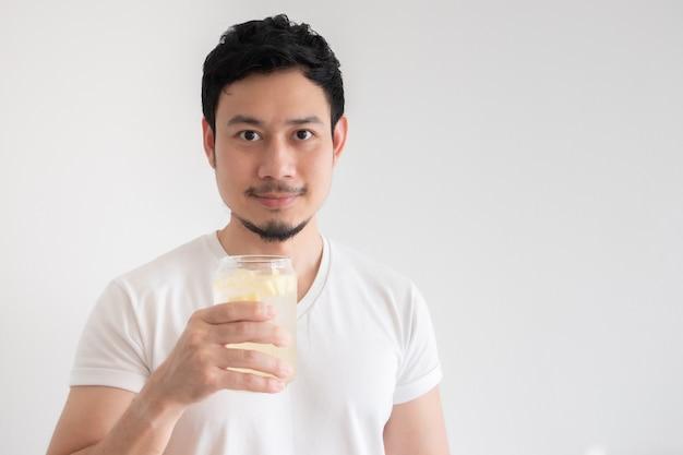 L'uomo asiatico sta bevendo la soda al limone ghiacciata su sfondo bianco isolato.