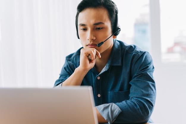 L'uomo asiatico sta discutendo online con i suoi subordinati
