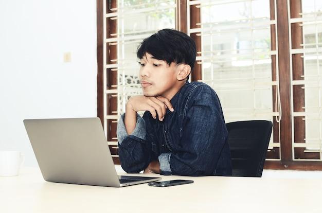 L'uomo asiatico è seduto davanti al laptop con un'espressione seria
