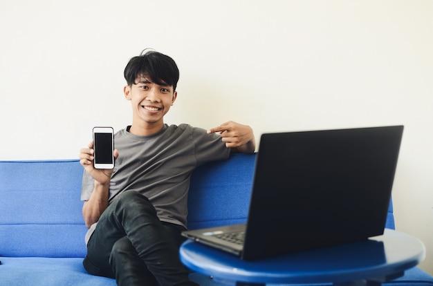 L'uomo asiatico è seduto sul divano usando un telefono cellulare