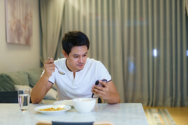 Un uomo asiatico usa il cellulare per chattare con un amico o controllare la posta elettronica mentre cena a casa la sera.