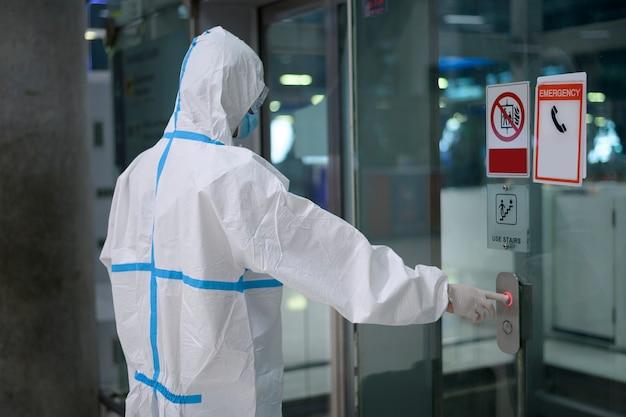 Un uomo asiatico indossa una tuta in ppe nell'ascensore dell'aeroporto, viaggio di sicurezza, protezione covid-19, concetto di allontanamento sociale