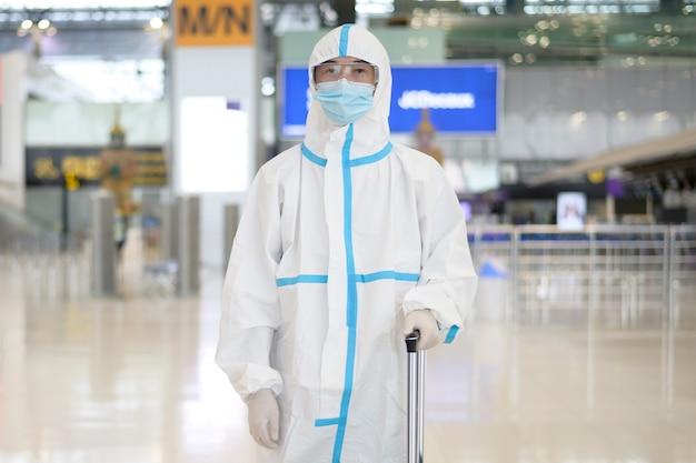 Un uomo asiatico indossa una tuta ppe in aeroporto internazionale, viaggi di sicurezza, protezione covid-19, concetto di allontanamento sociale.