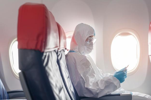 Un uomo asiatico indossa una tuta protettiva a bordo di un aereo