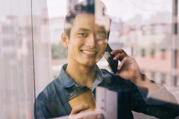 L'uomo asiatico sta lavorando vicino alla porta di vetro