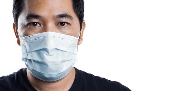 Uomo asiatico isolato che indossa una maschera usa e getta su un colore bianco