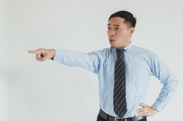 Uomo asiatico manager che indossa camicia blu e cravatta con espressione arrabbiata che punta su sfondo bianco