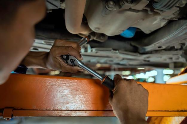 Il meccanico asiatico dell'uomo sta riparando il motore sull'ascensore dell'automobile.