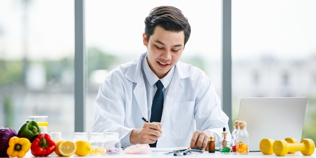 Uomo asiatico in uniforme medica che guarda e pensa alle pillole e prende appunti mentre lavora in una clinica moderna