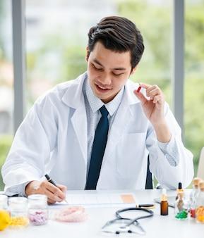 Uomo asiatico in uniforme medica che mostra la pillola e prende appunti mentre lavora in una clinica moderna