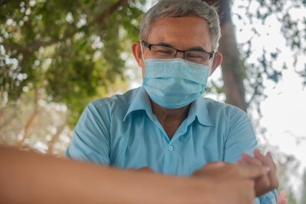 La maschera per il viso da uomo anziano asiatico impedisce al coronavirus covid19 di mantenere le distanze sociali