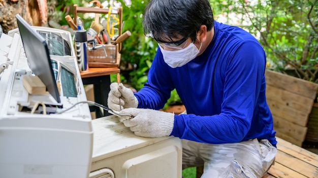 Uomo asiatico che impara online e ripara il condizionatore d'aria a casa. nuova vita normale dopo il covid-19. lock down e auto-quarantena. resta a casa e distanziamento sociale.