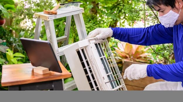 Uomo asiatico che impara online e ripara il condizionatore d'aria a casa. distanziamento sociale e nuovo stile di vita normale.