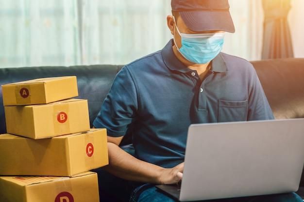 Vendite online uomo asiatico. il venditore prepara la scatola di consegna per il cliente o l'e-commerce. concetto previene la diffusione di germi e batteri ed evita infezioni corona virus [covid-19]