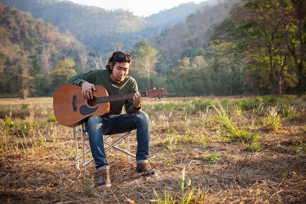 Uomo asiatico che suona la chitarra acustica sul posto