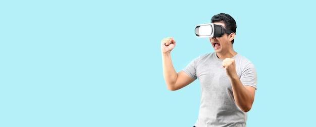 Uomo asiatico che gioca a un videogioco vr con occhiali per realtà virtuale e faccia shock e sorpresa