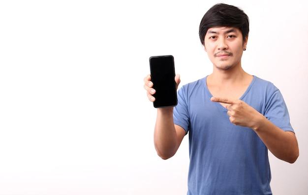 Uomo asiatico che indica barretta che tiene telefono cellulare su priorità bassa bianca.