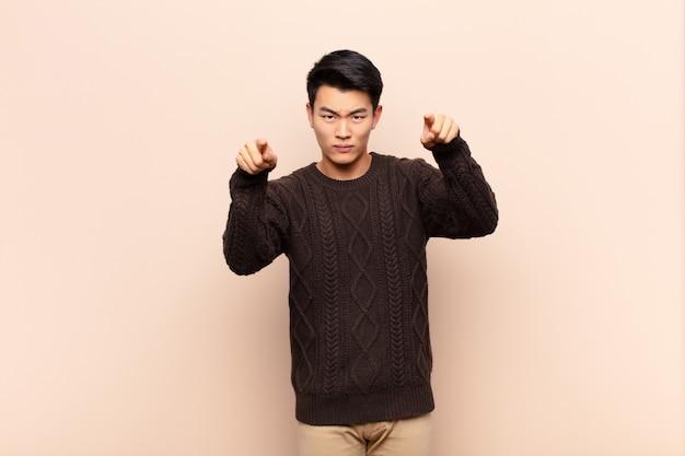 Uomo asiatico che punta in avanti con entrambe le dita e l'espressione arrabbiata, che ti dice di fare il tuo dovere