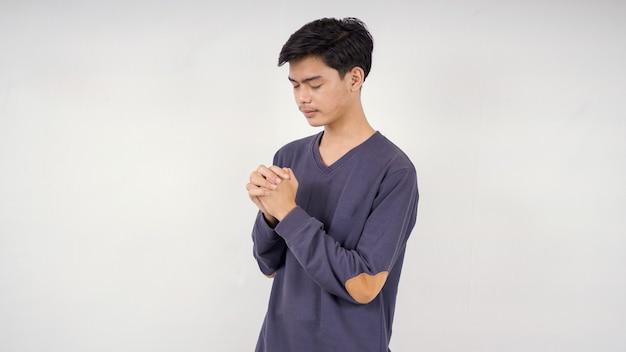 Uomo asiatico che prega isolato su sfondo bianco