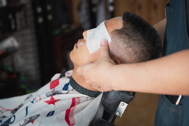Uomo asiatico che riceve il massaggio sulla sua testa dopo il taglio di capelli finito dal barbiere professionista nel negozio di barbiere.