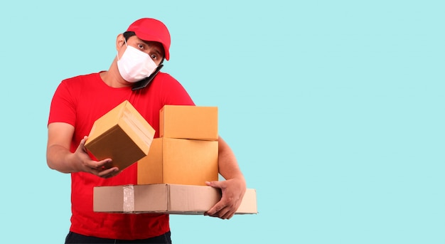 Uomo asiatico in berretto rosso, indossando la maschera per proteggere da germi e virus. in sospeso con pacco postale in scatole di cartone isolato tenendo il telefono cellulare in studio