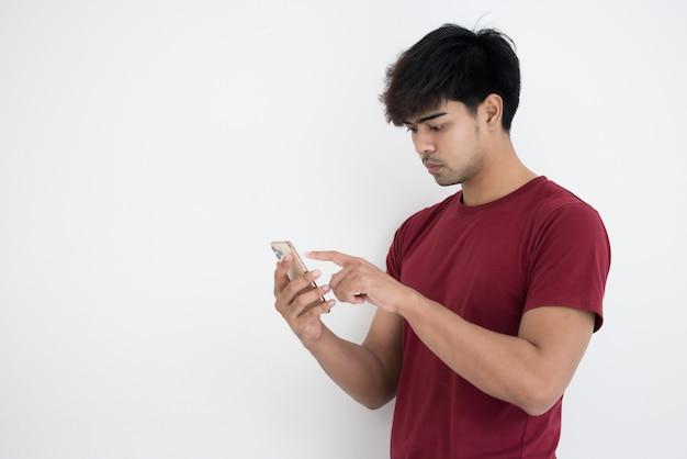 Uomo asiatico in maglietta rossa utilizza lo smartphone