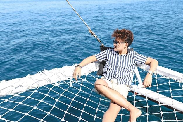 Uomo asiatico che si rilassa sulla rete del catamarano e si gode la vista sull'oceano