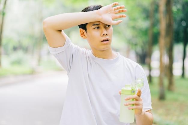 Uomo asiatico che riposa dopo aver fatto jogging nel parco