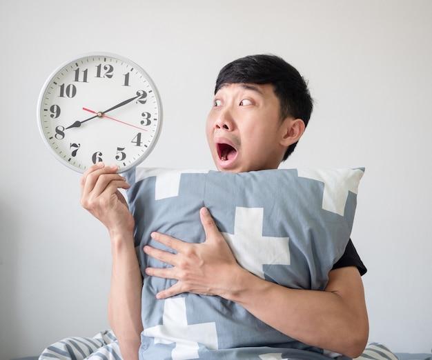 L'uomo asiatico ha scioccato il viso e guarda l'orologio in mano e abbraccia il cuscino svegliarsi tardi concetto