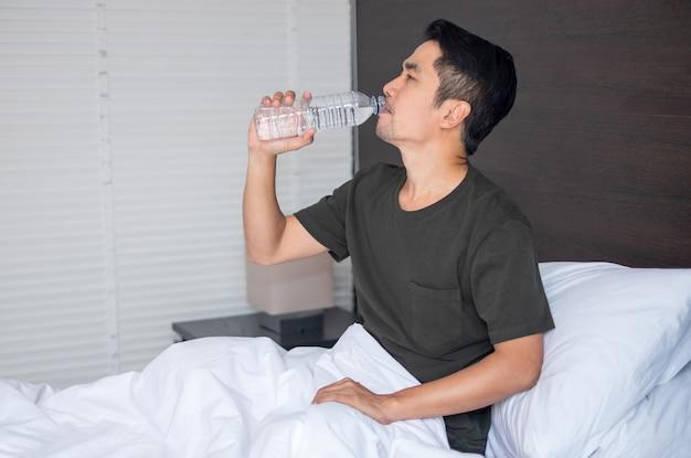 Uomo asiatico seduto e bevendo a letto