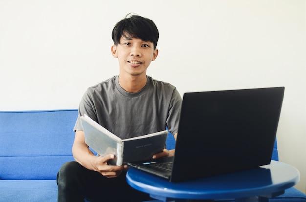 Uomo asiatico seduto sul divano con un'espressione allegra