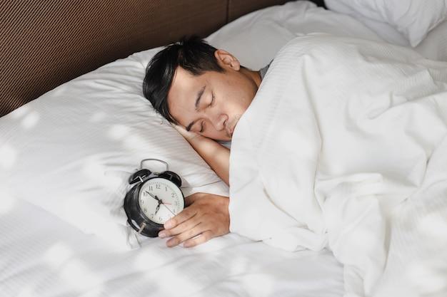 Uomo asiatico che dorme sul letto sotto la coperta con la sveglia che mostra le 7 in punto