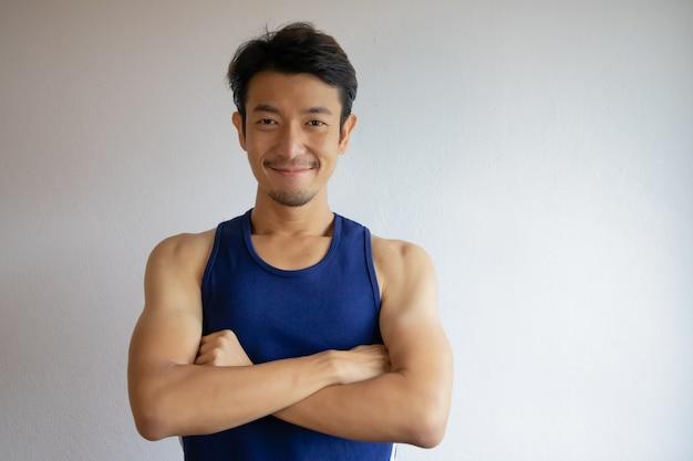 Sorriso dell'uomo asiatico e braccio incrociato