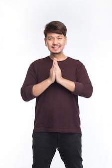 Uomo asiatico sorriso e saluto dal rispetto tradizionale tailandese, sawatdee, isolato su sfondo bianco