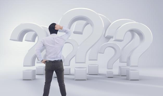 Uomo asiatico che si leva in piedi davanti al grande punto interrogativo