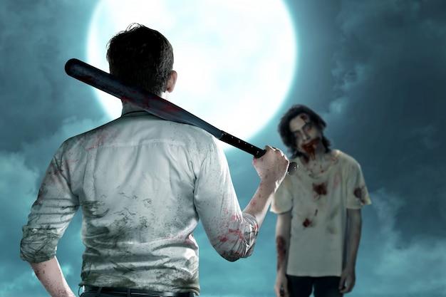 Uomo asiatico che sta con una mazza da baseball sulla sua mano che affronta gli zombie