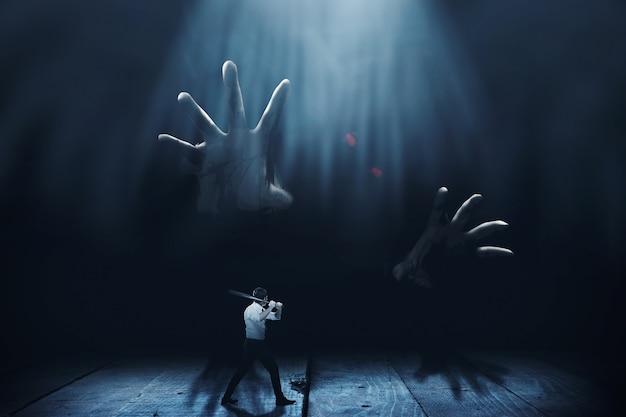 Uomo asiatico in piedi con una mazza da baseball in mano pronto ad attaccare zombi giganti con sfondo scuro