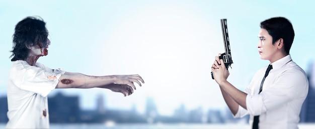 Uomo asiatico che sta con una pistola sulla sua mano pronta ad attaccare gli zombie