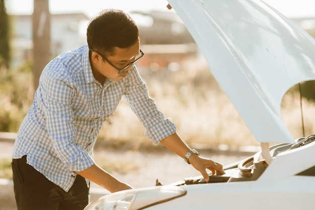 L'uomo asiatico sta davanti all'auto controllando le condizioni dell'auto dopo un'auto rotta. macchina rotta sulla strada. il servizio di emergenza ha rotto la macchina.