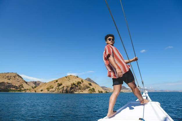 Uomo asiatico in occhiali da sole in posa sul bordo della barca con vista sul mare e colline a labuan bajo