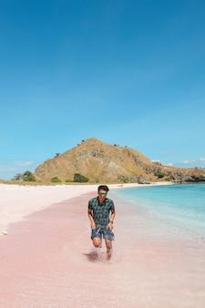 Uomo asiatico in occhiali da sole che corre sulla spiaggia di sabbia rosa a labuan bajo