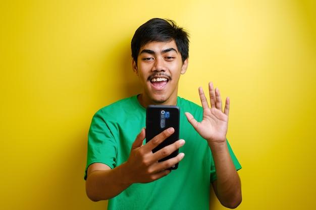 Uomo asiatico che scatta foto selfie o fa una videochiamata a casa, sorride alla telecamera e saluta. felice espressione allegra su sfondo giallo