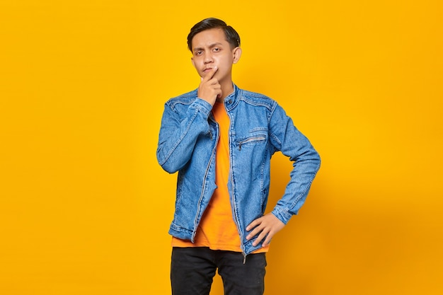 L'uomo asiatico pensa a qualcosa e le tocca il mento su sfondo giallo